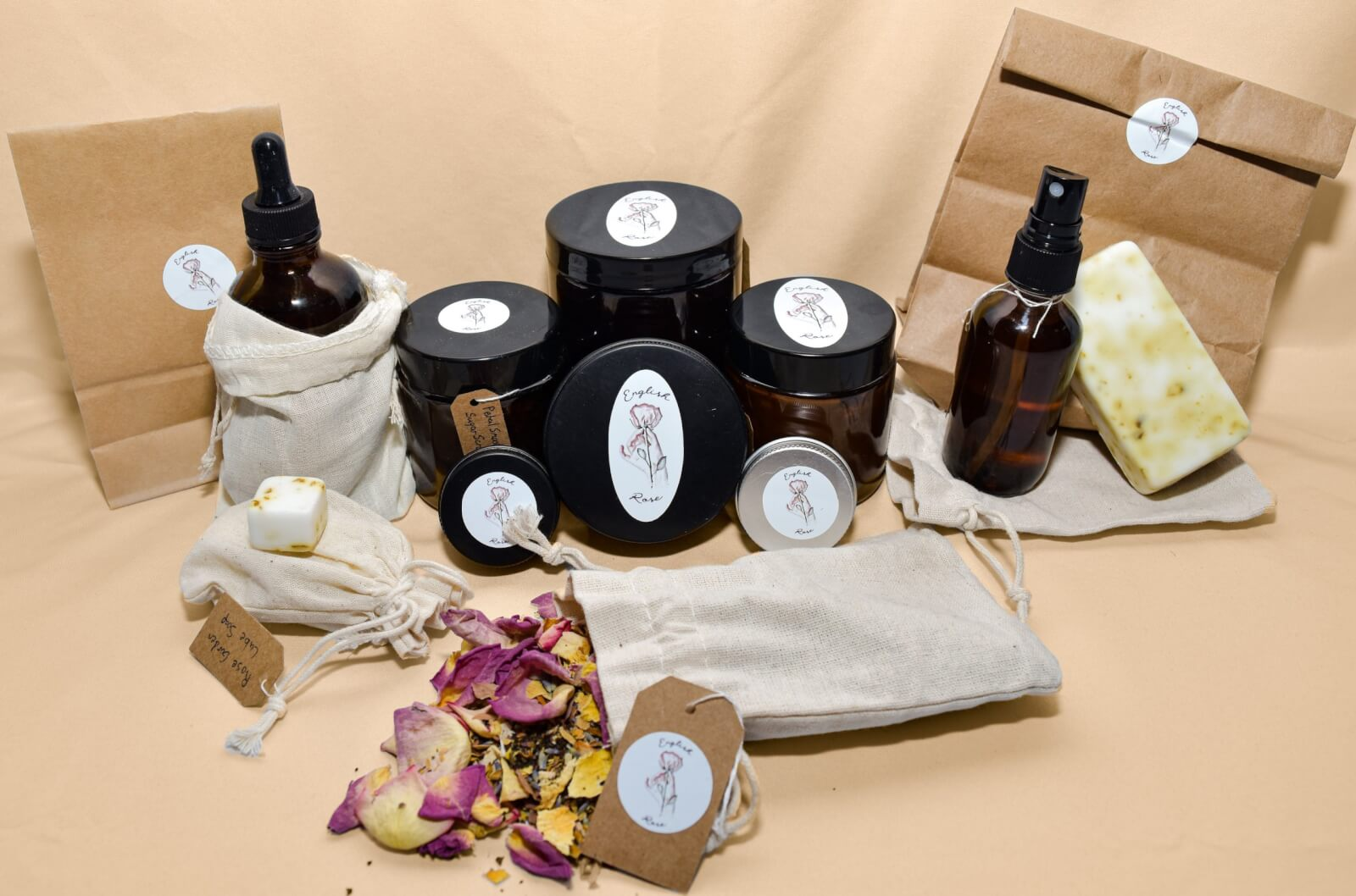 A collection of English Rose skincare products, including jars, tins, spray bottles, bar soap and linen bags with potpourri