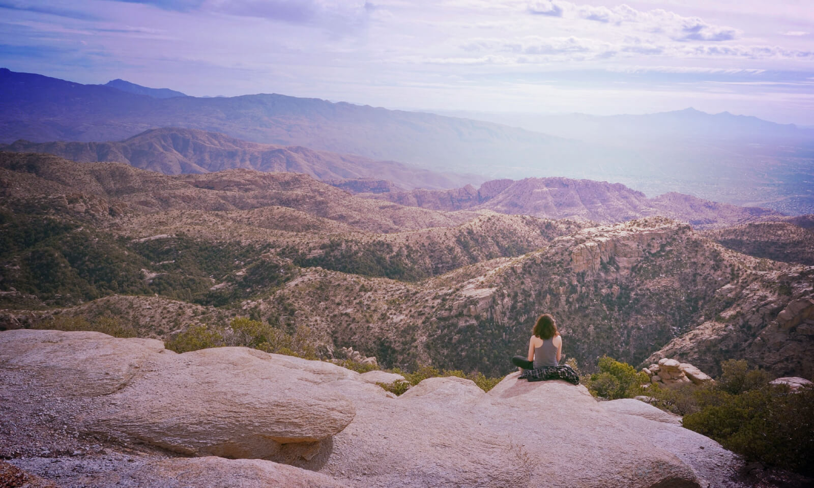 Woman sitting on rocks on Mt. Lemmon facing the view.