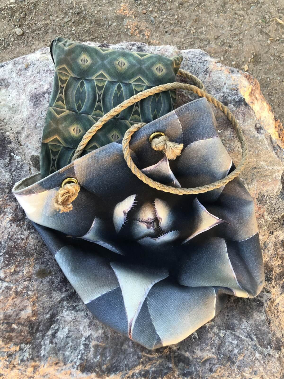 A bag with a cactus design and rope handles is laid on a rock with a pillow inside.