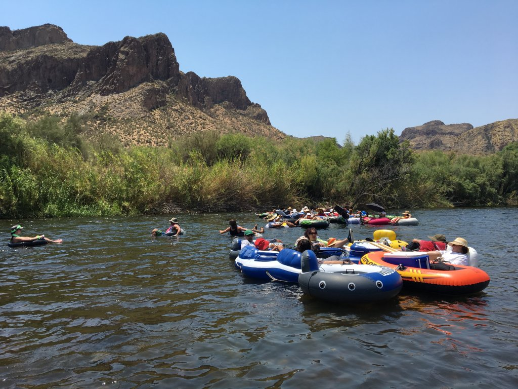 Tubers float along the Salt River in Arizona with greenery and mountains in the background.