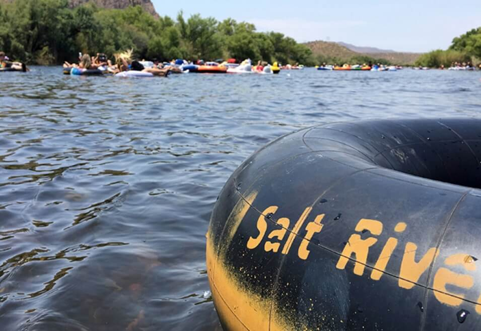 A black and yellow tube, labeled Salt River, floats in the Salt River in Arizona with tubers in the background.