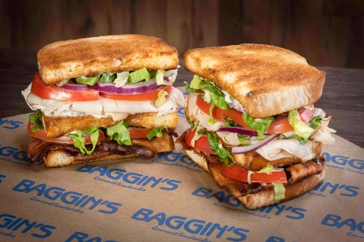A toasted club sandwich cut in half sits on a Baggins wrapper.