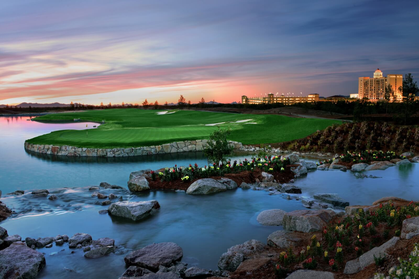 The water hazards at the Casino Del Sol Sewailo Golf Club at sunset with the casino and hotel in the distance.
