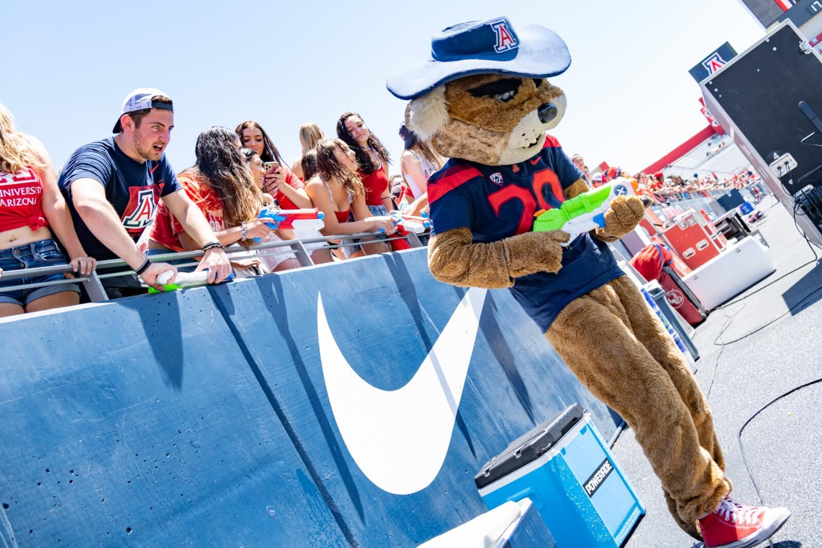 University of Arizona Mascot, Wilbur, shoots a large water gun while a crowd of U of A students mingle behind him.
