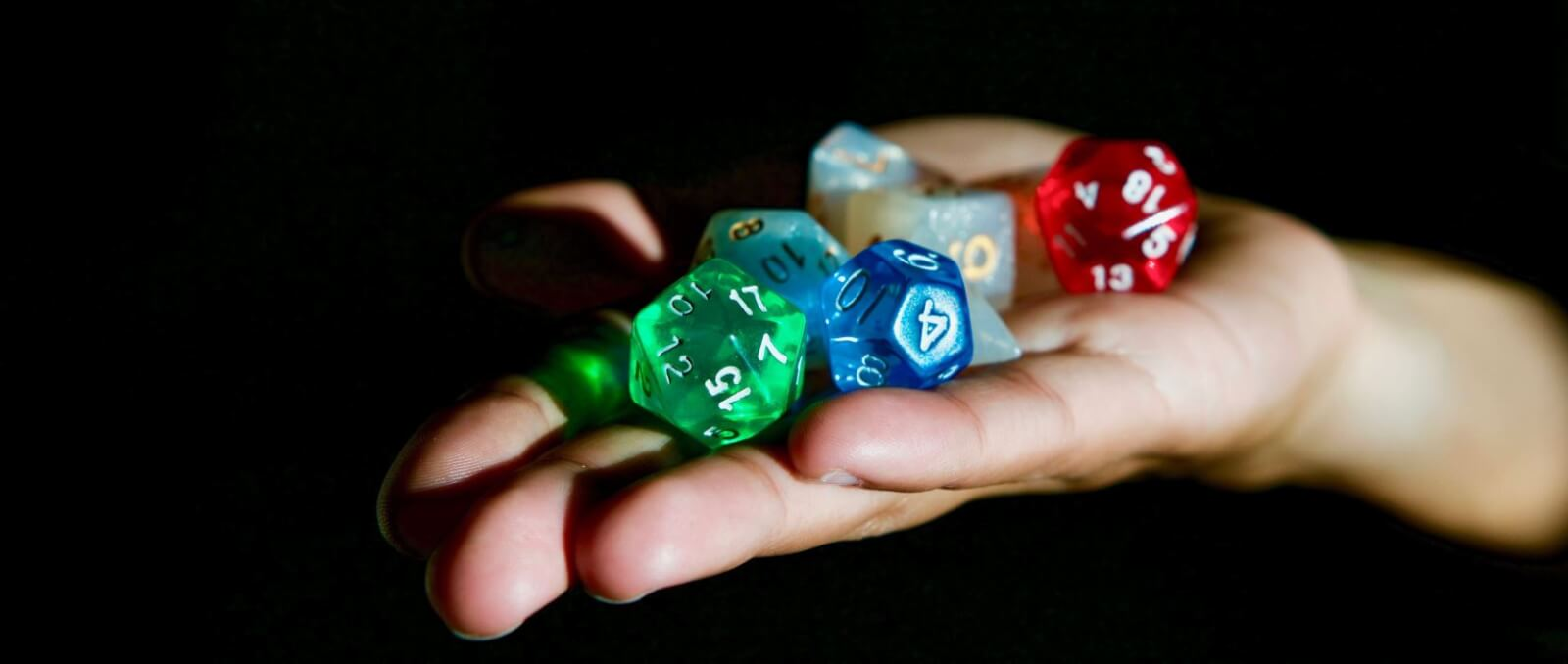 Open hand with multi-colored dice.