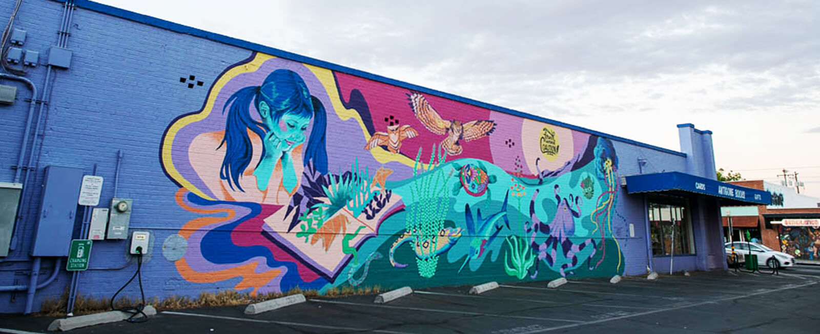 A colorful mural of a young girl reading books.