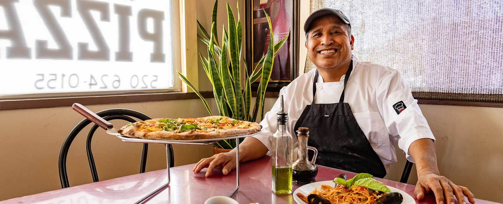 A Hispanic man wearing a white chef's coat and apron sits at a table with a pizza on a stand, a pasta dish and oil and vinegar bottles.