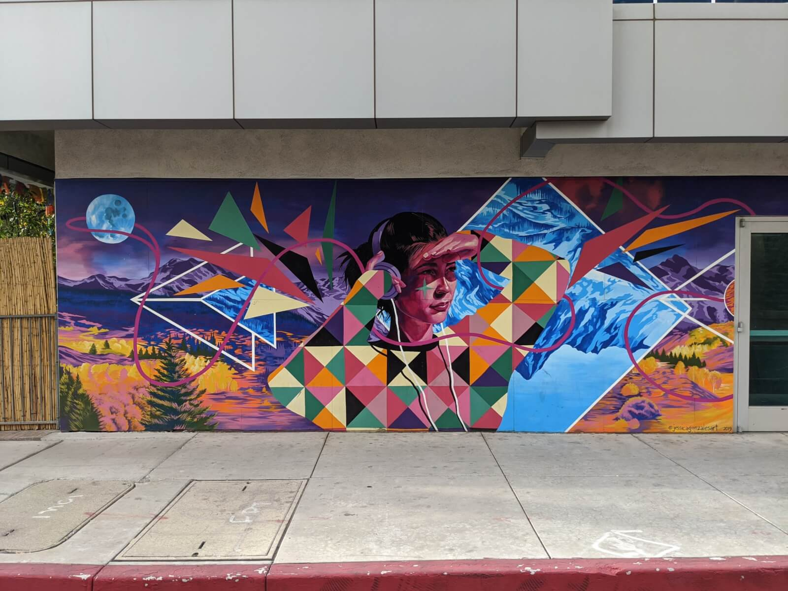 A close up of a colorful mural of a young woman wearing headphones