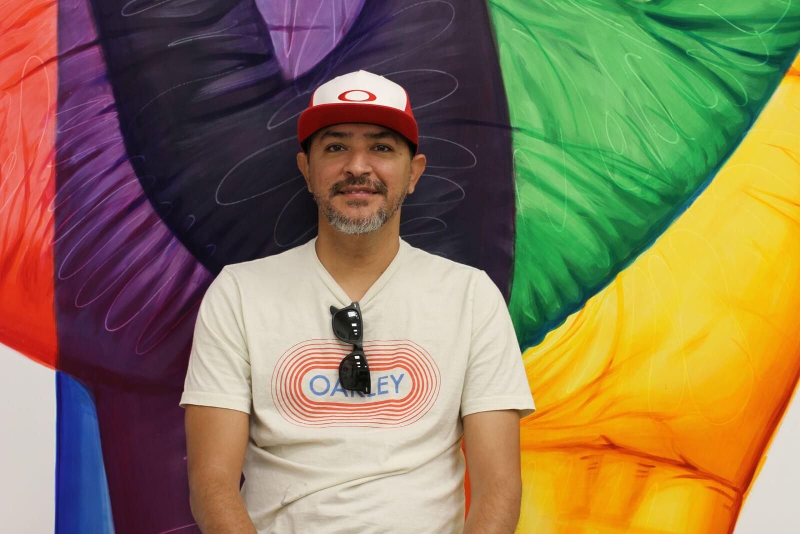 Muralist Ignacio Garcia smiles in front of a colorful mural