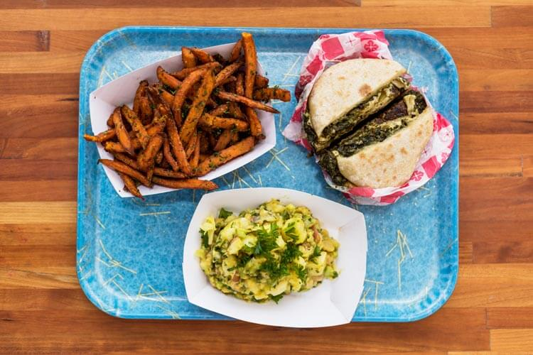 A blue tray sits on a wooden table filled with a burger, sweet potato fries and a salad.