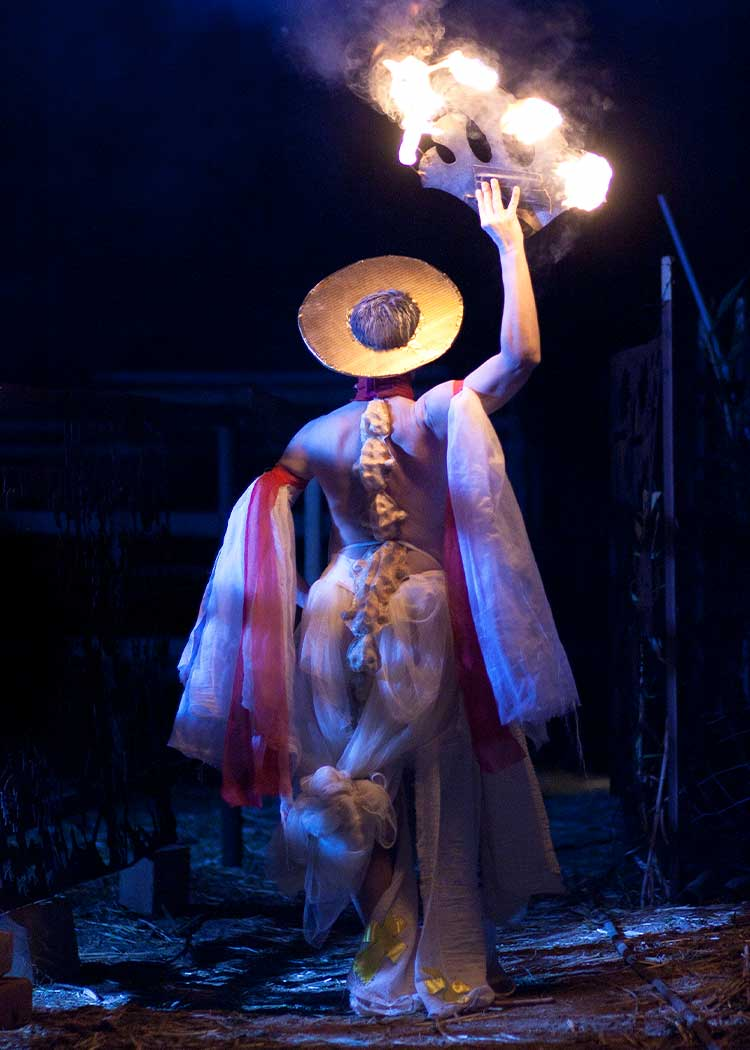 A woman in a colorful costume and yellow hat walks across stage holding a flaming circle in one hand.