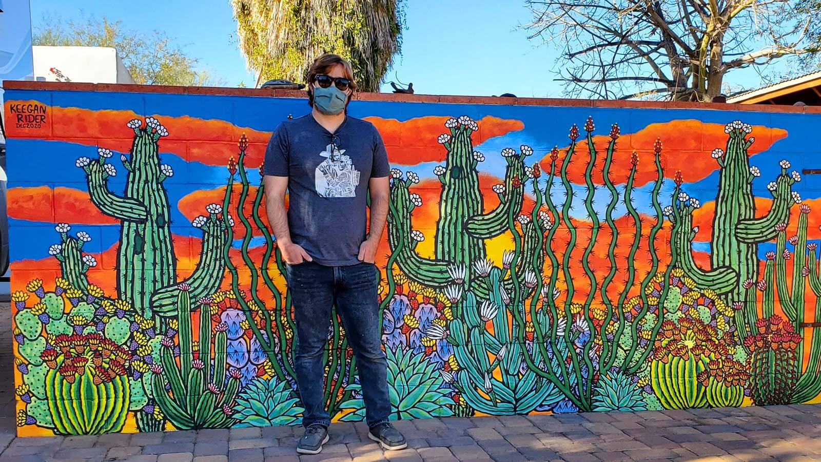A man wearing a mask and sunglasses stands in front of a colorful mural of cactus plants in bloom.