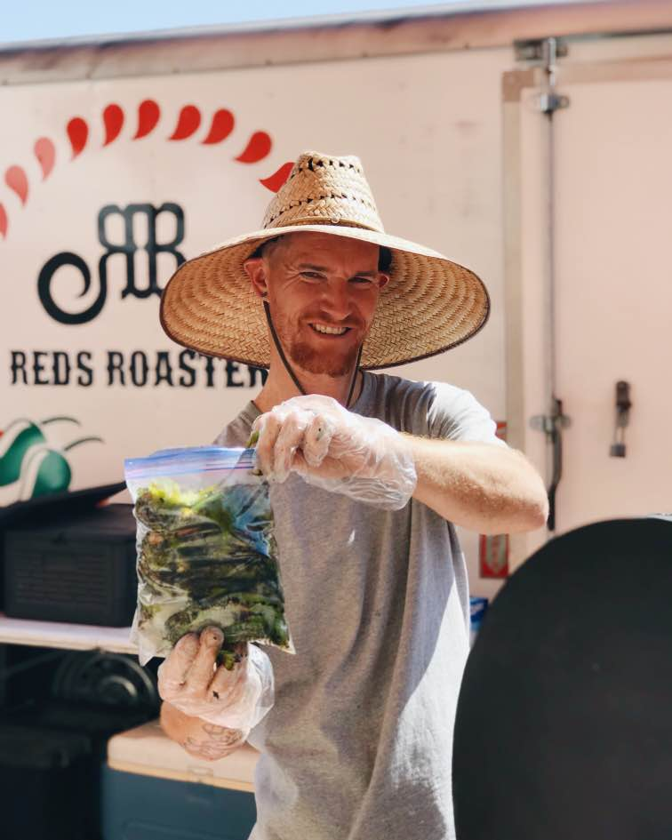 Kris Young of Red's Roasters poses with a bag of freshly roasted green chiles, while wearing a straw hat in front of his company trailer.