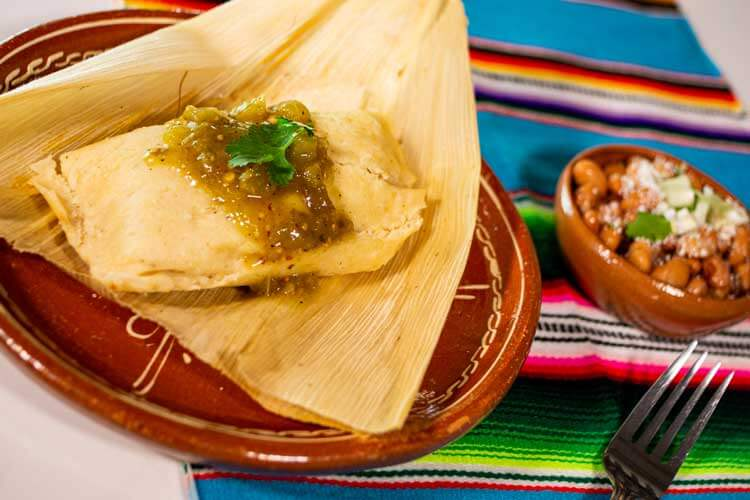 A close up of a tamale sitting on a colorful placemat with a side of beans.
