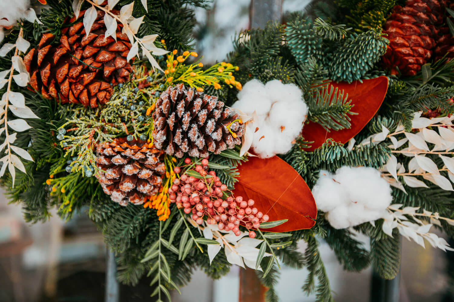 A close up of a wreath decorated with pine cones, berries, and stems sold at Thistle, in Tucson, Arizona