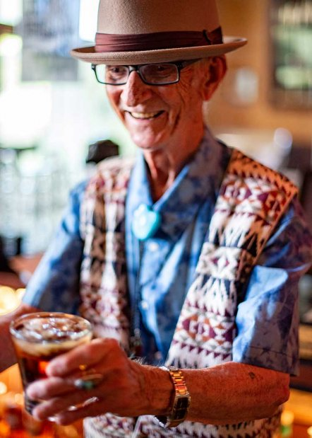 A man wearing a blue checked shirt and a southwest style vest serves a drink at TIger's Taproom in Hotel Congress