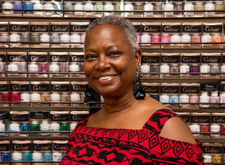 A black woman wearing a red and black top stands in front of a wall of nail polish.