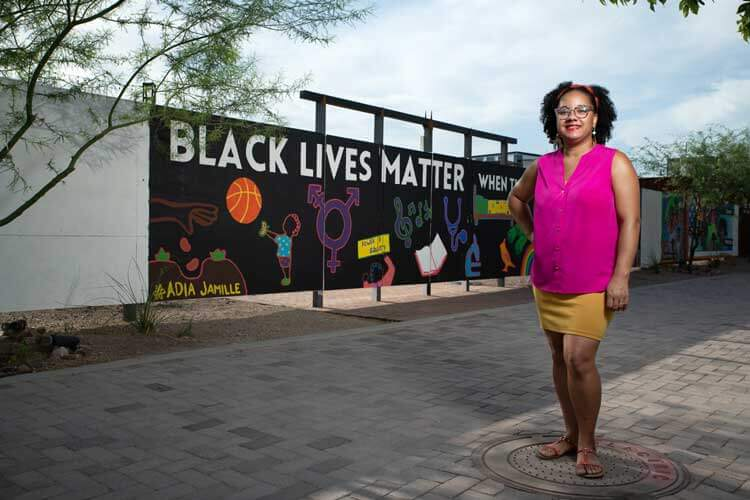 A black woman in a bright pink tank top and yellow skirt stands in front of her black lives matter mural.