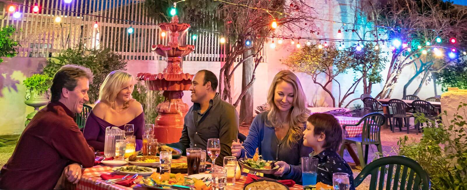 Two adult couples and one young child enjoy an Italian feast on the patio at Caruso's in Tucson, AZ.