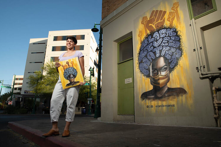 Camila Ibarra stands in front of her black lives matter mural at Hotel Congress.