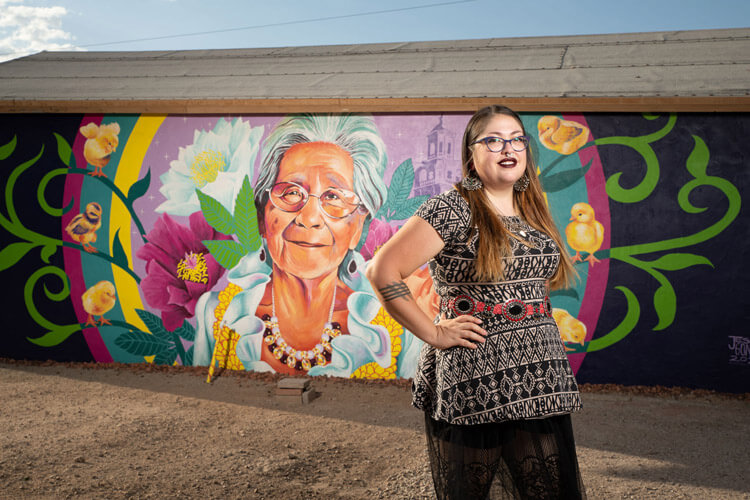 A Hispanic woman stands in front of her colorful mural of a grandmother painted on a wall.