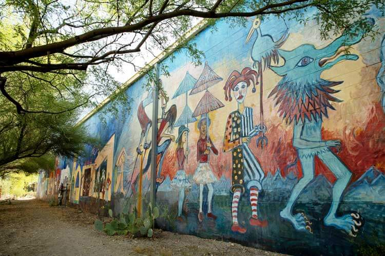 A colorful mural of mythical figures are painted on a wall.
